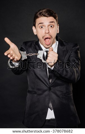 Portrait young businessman in black suit looking at camera with showing handcuffs. People and crime financial concept. Image on a black background. - stock photo