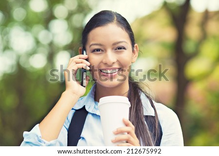 Portrait young businesswoman professional walking outdoors talking on cell smart phone drinking coffee from disposable paper cup. Multiracial Asian / Caucasian business woman smiling. Positive emotion - stock photo