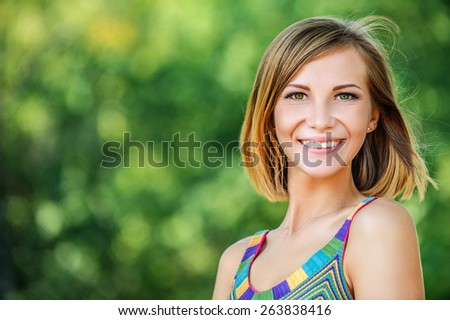 portrait young charming short-haired woman background summer green park - stock photo