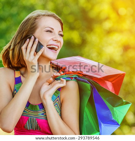 portrait young charming short-haired woman shopping bags behind background summer green park - stock photo