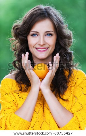 portrait young charming woman standing holding tangerine background summer green park - stock photo