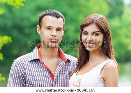 portrait young couple love standing next background summer green park - stock photo