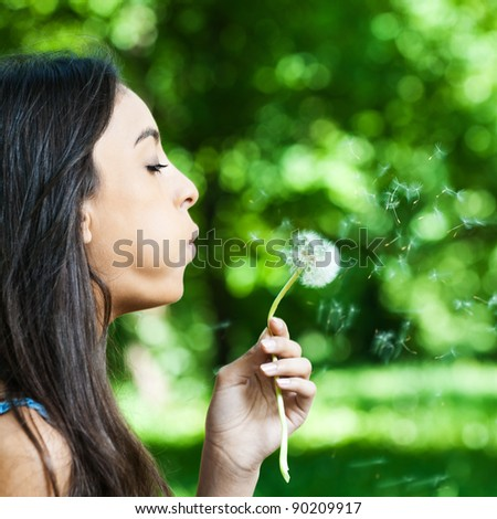 portrait young dark-haired girl profile blowing dandelion - stock photo