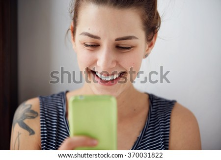 Portrait young funny woman happy, something on cell phone while texting receiving good sms text message isolated grey wall background. Human face expression emotion reaction - stock photo