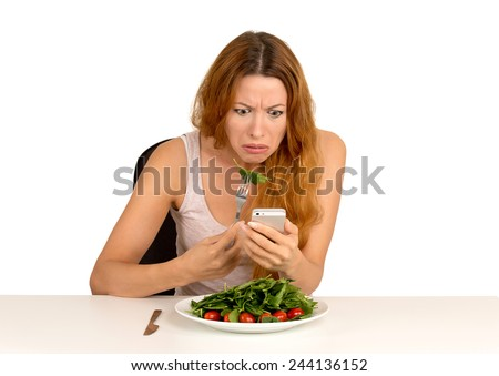 portrait young girl eating green salad looking at phone seeing bad news or photos shocked confused face expression isolated on white background. Human emotion  - stock photo