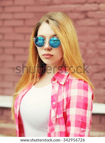 Portrait young girl wearing a checkered shirt and sunglasses in city - stock photo