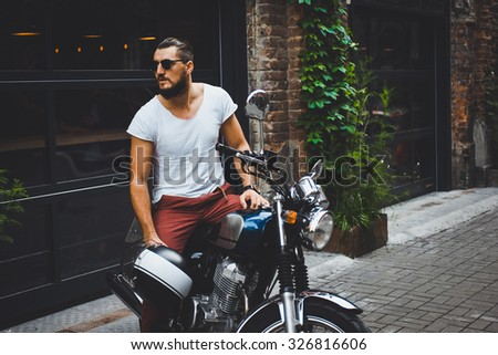 portrait young guy with a beard and mustache with sunglasses and white T-shirt posing on the street vintage man, fashion men, hipster street casual a motorcycle - stock photo