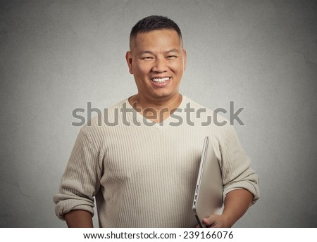 Portrait young handsome happy man holding laptop smiling standing isolated on office grey wall background. Positive face expression emotion. Computer educated guy student employee concept  - stock photo