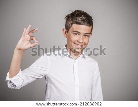 Portrait young happy man, teenager showing Ok sign, hand gesture, isolated grey wall background. Positive human emotions, facial expressions, nonverbal communication, body language, signs, symbols - stock photo