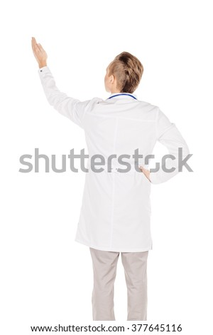 Portrait young male doctor in white coat directional pointing at distance looking away. People and medicine concept. Image isolated on a white background.