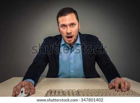 Portrait young man in blue shirt and jacket looking at the camera with amazement, sitting at a desk near a computer isolated on gray studio background. Human emotion, facial expression. Closeup - stock photo