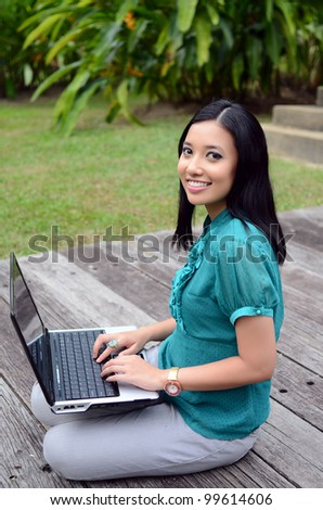 Portrait young pretty Asian muslim college girl with laptop and smile - stock photo