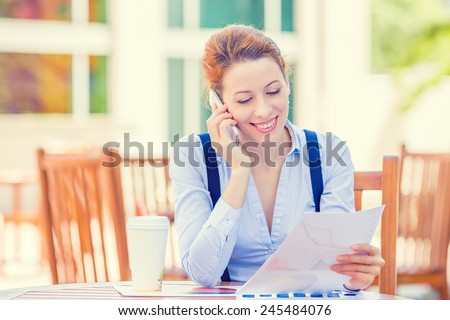 Portrait young professional woman talking on mobile phone reviewing documents papers outside corporate office isolated city building background. Positive face expression emotion, life success concept - stock photo
