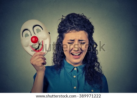 Portrait young upset crying screaming woman holding a clown mask expressing cheerfulness happiness isolated on gray wall background. Human emotions  - stock photo