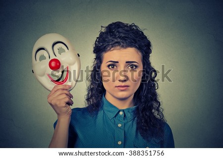 Portrait young upset worried woman with sad expression holding a clown mask expressing cheerfulness happiness isolated on gray wall background  - stock photo