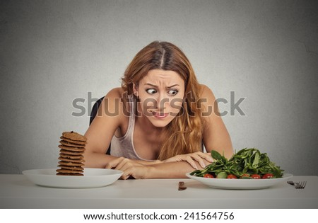 Portrait young woman deciding whether to eat healthy food or sweet cookies she is craving sitting at table isolated grey wall background. Human face expression emotion reaction Diet nutrition concept  - stock photo