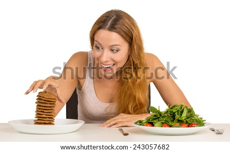 Portrait young woman deciding whether to eat healthy food or sweet cookies she is craving sitting at table isolated white background. Human face expression emotion reaction. Diet nutrition concept - stock photo