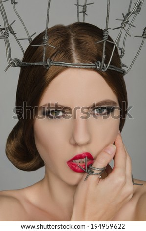 Portrait young woman in crown and ring of barbed wire