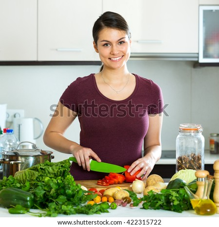 Portrait young woman preparing vegetarian meal and smiling at home