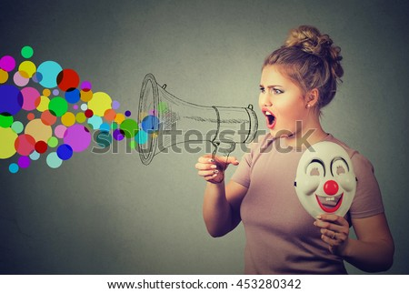 Portrait young woman with clown mask screaming in megaphone isolated on gray background. Negative face expression emotion feeling. Propaganda, breaking news, power, social media communication concept - stock photo