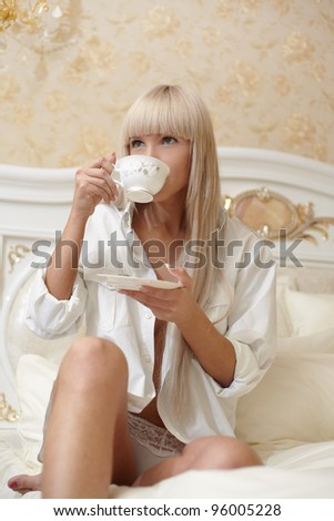 Portrait young woman with coffee in bedroom - stock photo