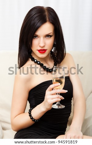 Portrait young woman with glass of champagne, girl with red lips wear evening dress, glamour vogue style, sensual looking at camera, sitting indoors - stock photo