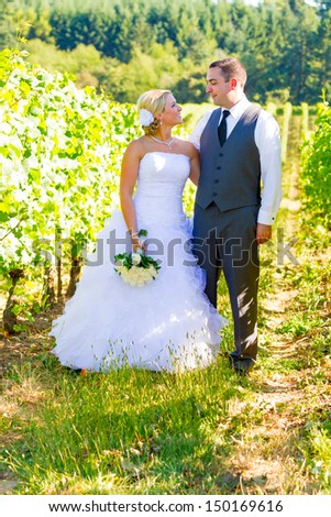 Portraits of a bride and groom outdoors in a vineyard at a winery in Oregon right after their ceremony and vows. - stock photo