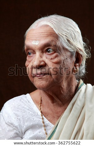 Portraits of an Indian senior woman looking on one side - stock photo