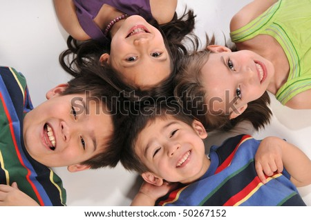 Portraits of children lying down on the floor ans smiling - stock photo
