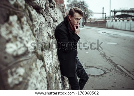 portraits of fashion man posing outside, grounge background - stock photo