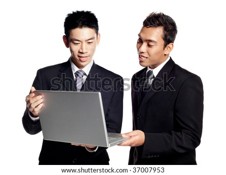 Portraits of two Asian Businessmen, Chinese and Malay, sharing business information on a laptop. Dressed formally in suit and tie. Shot in studio isolated on white - stock photo