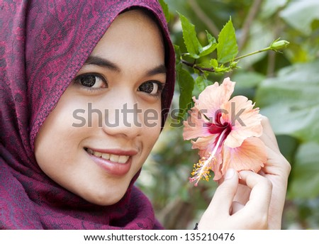 Portraits of young muslim woman holding a red hibiscus flower next to her face - stock photo