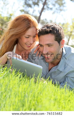 Portrat of couple laying down the grass with touchpad - stock photo