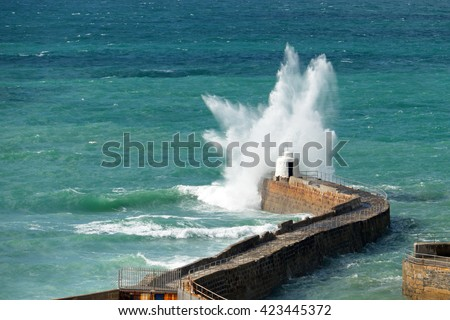 Portreath pier big white water wave splash, Cornwall England. - stock photo