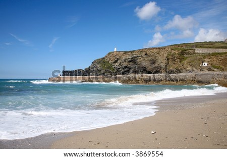 Portreath pier, the Pepperpot and Lookout and a wave breaking on the beach.