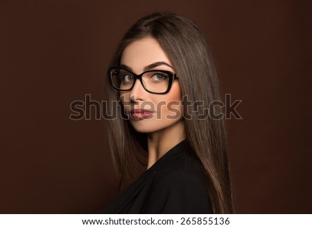 portret business woman in glasses and a black suit on a background