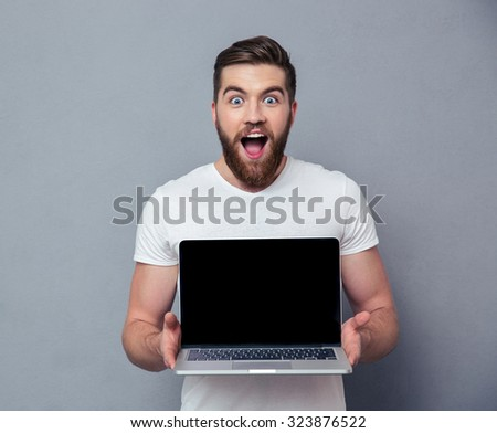 Portrit of a cheerful man showing blank laptop computer screen over gray background - stock photo