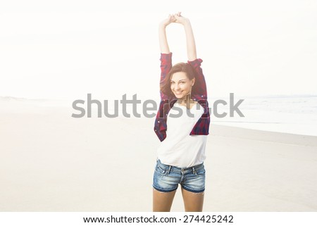 Portrtait of a happy girl at the beach enjoying the life - stock photo
