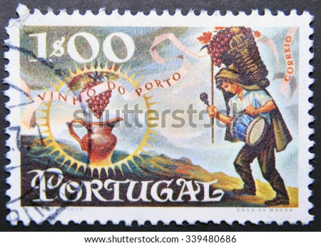 PORTUGAL - CIRCA 1970: a stamp printed in Portugal dedicated to wine of Oporto, shows Worker Carrying Basket of Grapes and Jug, Port Wine Export, circa 1970 - stock photo