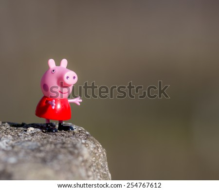 Portugal - January 10, 2015 : Figure of Pepa Pig from Astley Baker Davies / Entertainment One UK animations, standing on a rock in my farm, Povoa de Lanhoso - stock photo