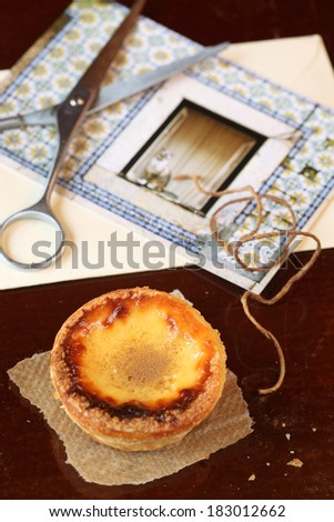 Portuguese Custard Tart and postcard on dark background. - stock photo