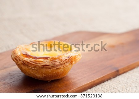 Portuguese egg custard tart, pastel de nata, served on a wooden board. These delicious bakes are also popular in South East Asia especially in Macau. - stock photo