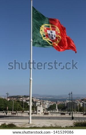 Portuguese flag flying on high point with overview of downtown Lisbon - stock photo