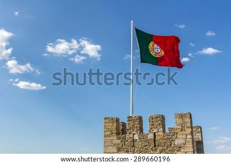 Portuguese Flag Waving Against Blue Sky - stock photo