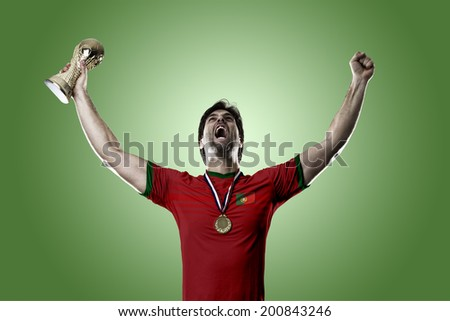 Portuguese soccer player, celebrating the championship with a trophy in his hand. On a green background.