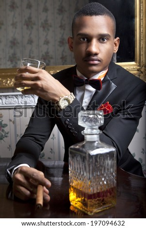 Posh, black man drinks whiskey in the hotel room - stock photo