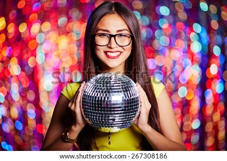 Posh girl in eyeglasses holding disco ball - stock photo
