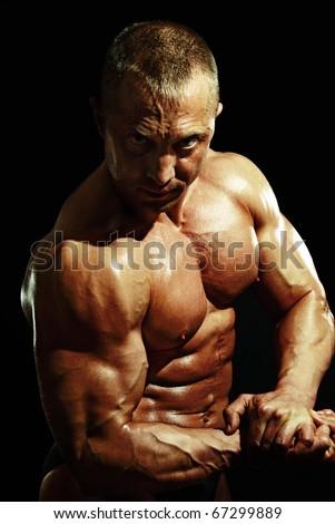 posing man bodybuilder on black background - stock photo