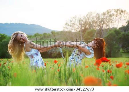 Posing two girls in poppy field on sunset - stock photo
