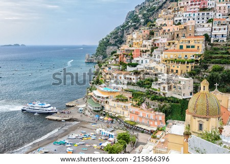 POSITANO, ITALY - SEPTEMBER 30 2012: Evening ferry boat arrives in Positano. Ferry service along the Amalfi coast is a popular form of transport for tourists and locals during the summer months. - stock photo